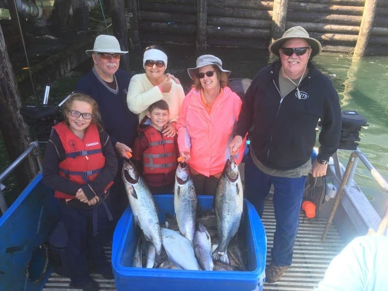 Kodiak Island Fishing Charters with Family of 6 holding King Salmon caught on Fish N' Chips Charters